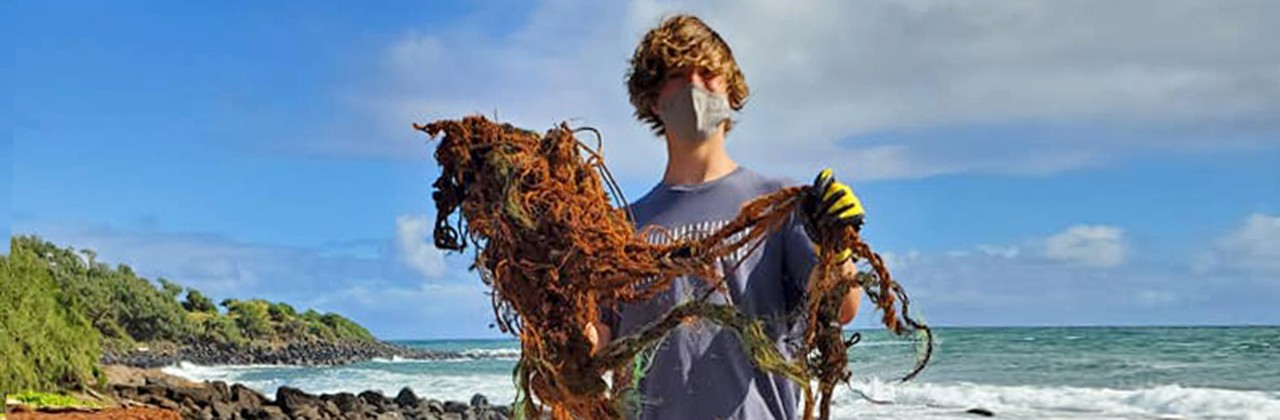 Volunteer removes marine debris off of remote coastline in Anahola, Hawaii on the Island of Kauai. In 2020 volunteers hauled away nearly 129,000 lbs of litter and marine debris from Kauai's coastal areas. Mahalo Volunteers!
