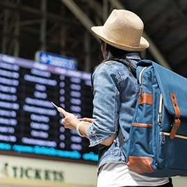 Woman at airport looking at arrival and departure screen