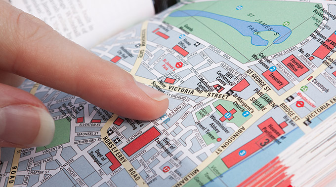 A finger points at an intersection on a paper map of London