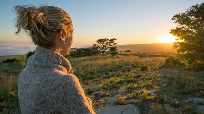 Woman looking at sunrise on the savannah in South Africa