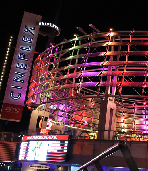 Colorfully lit exterior of the AMC Universal Cineplex 20 movie theater
