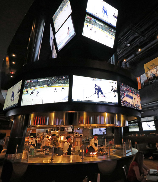 Interior of NBC Sports Grill & Brew showing the grill and many televisions