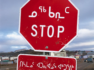 A stop sign in Iqaluit, Nunavut, with Inuktitut and English