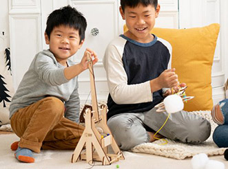 Two boys playing with KiwiCo learning kits
