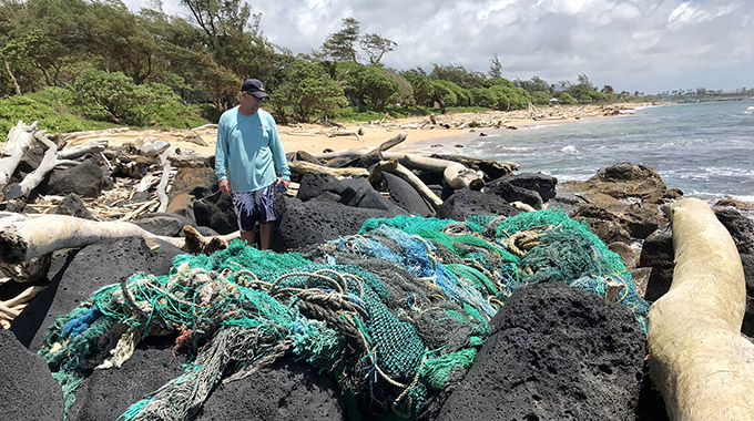 Surfrider Foundation Kauai Chapter volunteer Keith Rich assesses a large ghost net at Lydgate Beach.