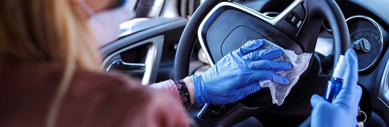 A masked woman disinfects a car steering wheel
