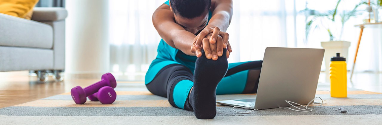 Woman doing stretches before exercising in her home