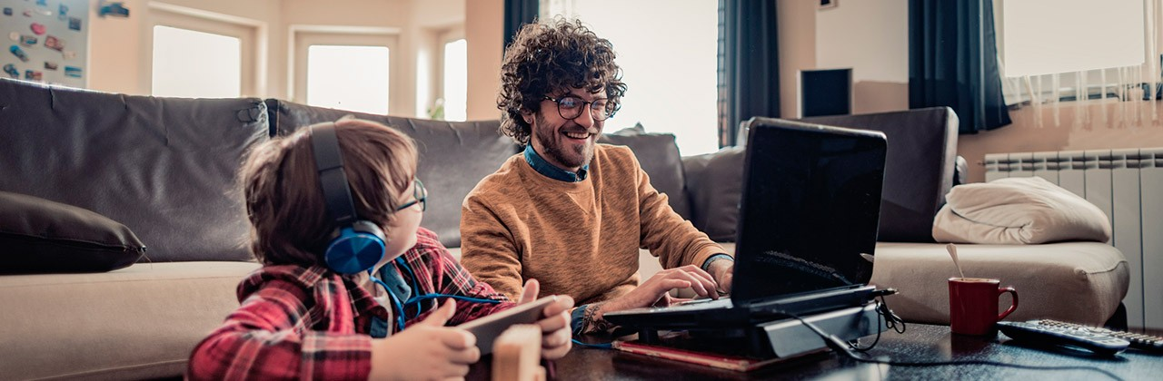 A father and son use mobile devices in their living room at home