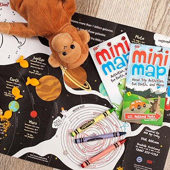 A stuffed monkey on top of mini maps and crayons