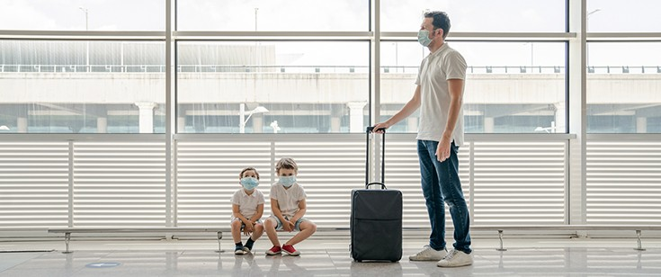 Man and children wearing masks at airport
