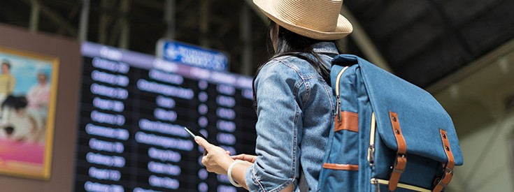 Woman looking at airport arrival and departure screen