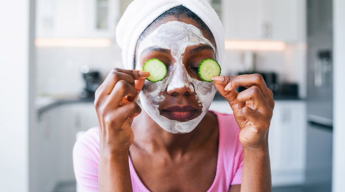 A woman applies face cream and cucumber slices to her face