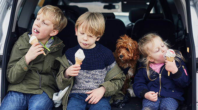 Three kids eat ice cream while sitting in the back of a car, with a dog