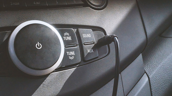 An audio aux in cable plugged into a car radio