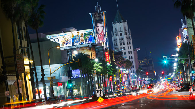 Hollywood Boulevard at night facing east, with lights from traffic and signs.