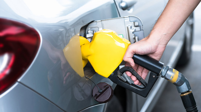 Yellow gas pump fueling silver car
