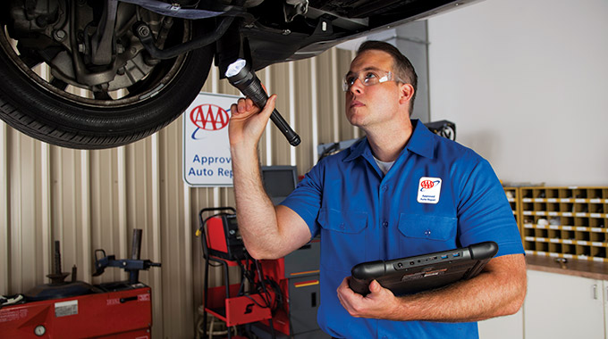 A AAA Approved Repair technician inspects the bottom of a car